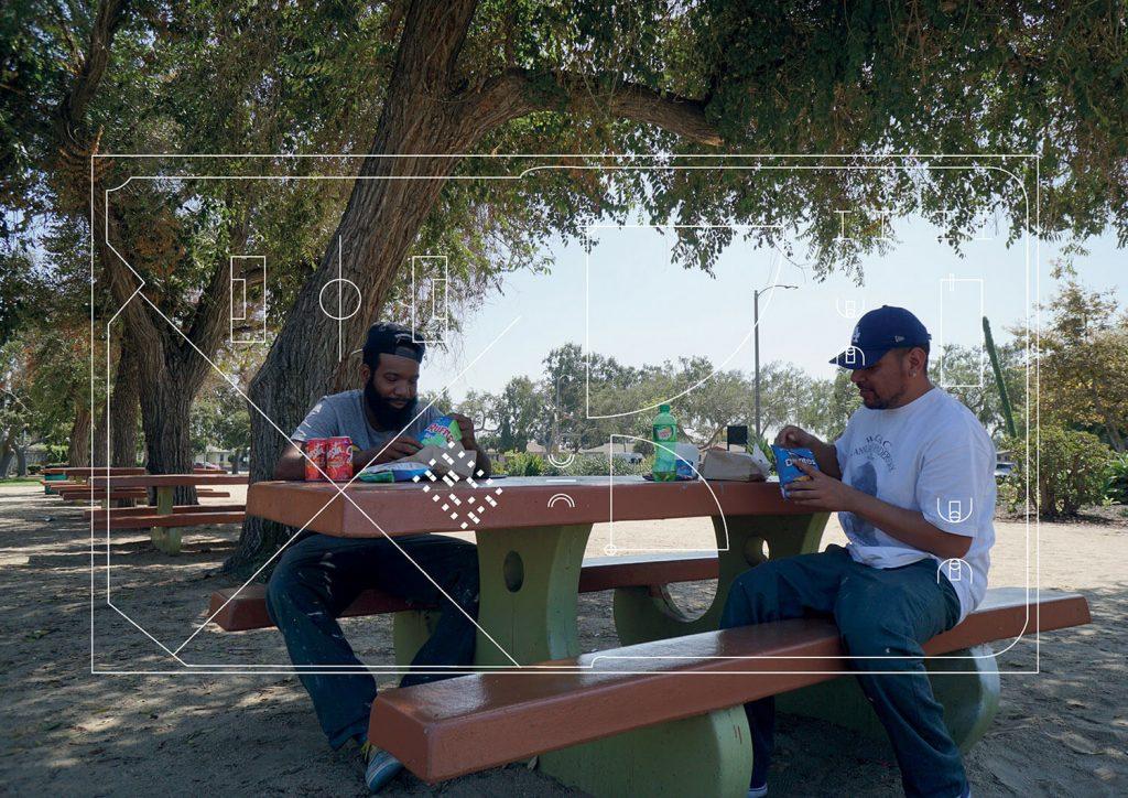 Men eating snacks at a picnic table